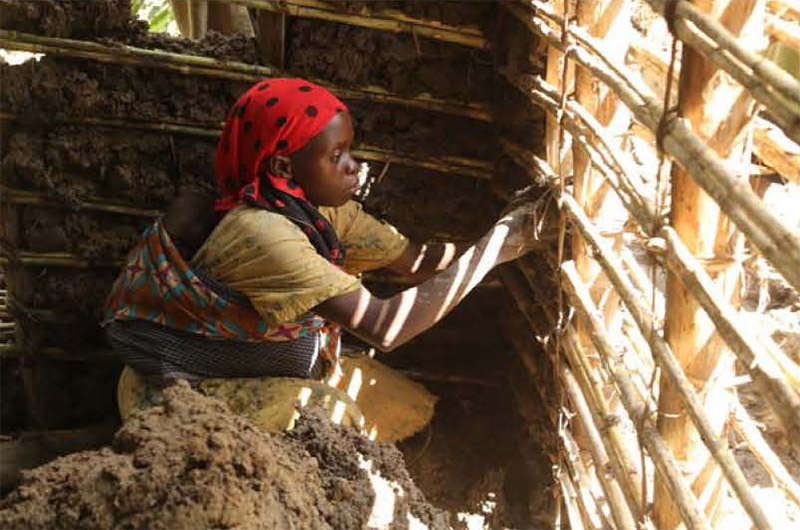 A Batwa woman with baby on her back adds mud to create house walls.