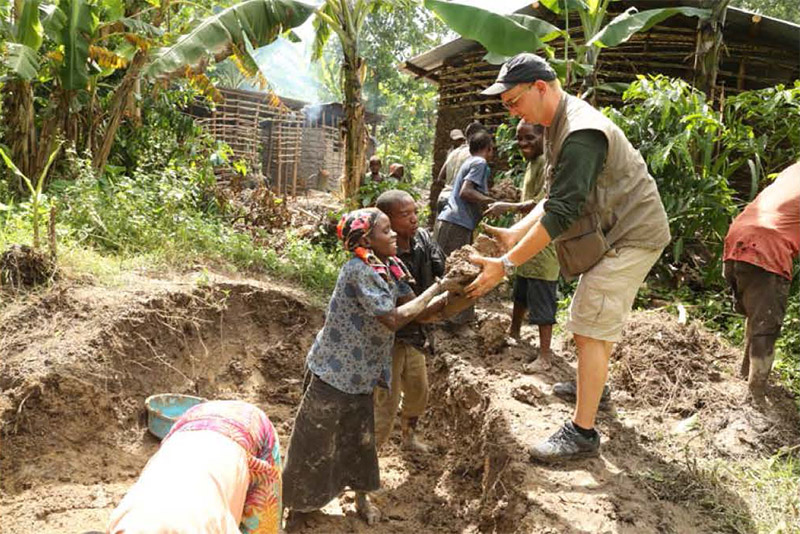 Dr. Robert Johnson from the RSF helps excavate mud to build a Batwa home.