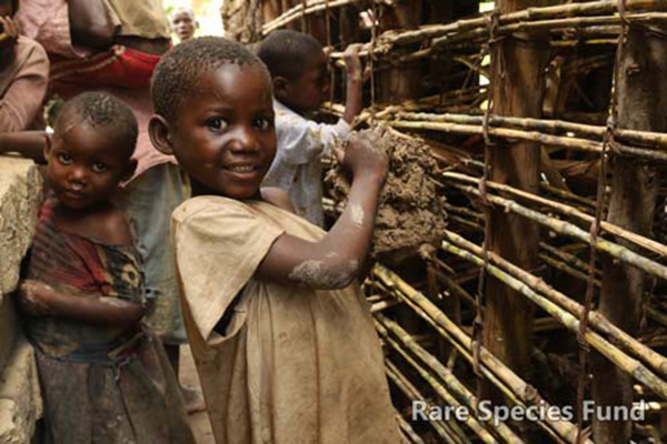 Batwa children helping build a wall.