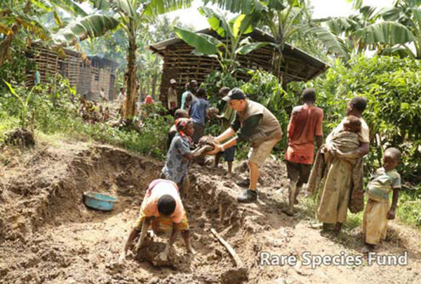 RSF staff helps dig mud for building a home.