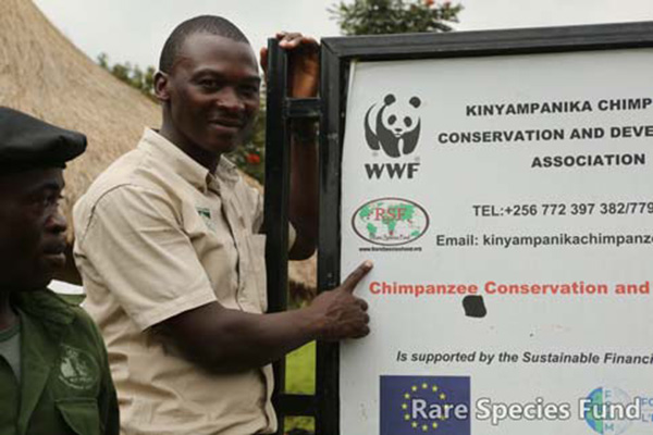 RSF Ambassador for Uganda, Kiweewa Petrus Kkukumba shows the Rare Species Fund logo on the KICHIDA sign.